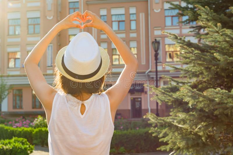 帽子的女孩显示与她的手指的心脏,站立与她,看日落,背景城市样式 图库摄影