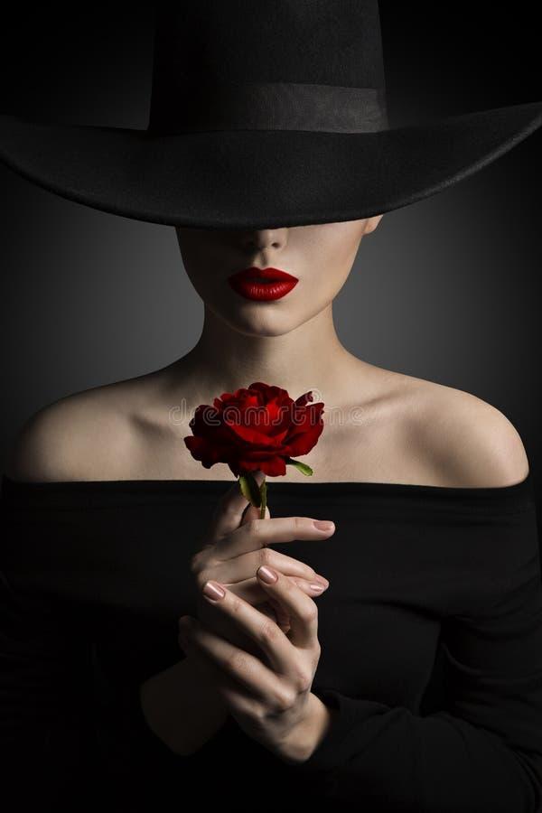 帽子的妇女在手上的拿着罗斯花,时装模特儿秀丽 免版税库存图片