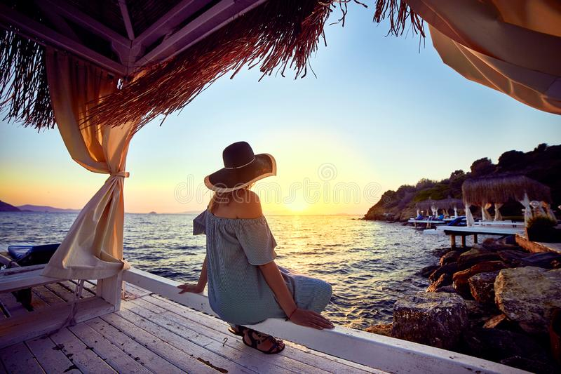 帽子的妇女放松由一种豪华海滩前的旅馆手段的海在日落享受完善的海滩假日假期的  图库摄影