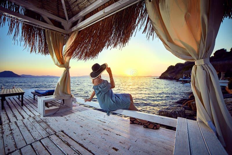 帽子的妇女放松由一种豪华海滩前的旅馆手段的海在日落享受完善的海滩假日假期的  库存照片