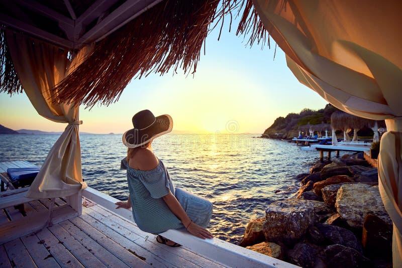 帽子的妇女放松由一种豪华海滩前的旅馆手段的海在日落享受完善的海滩假日假期的  库存图片