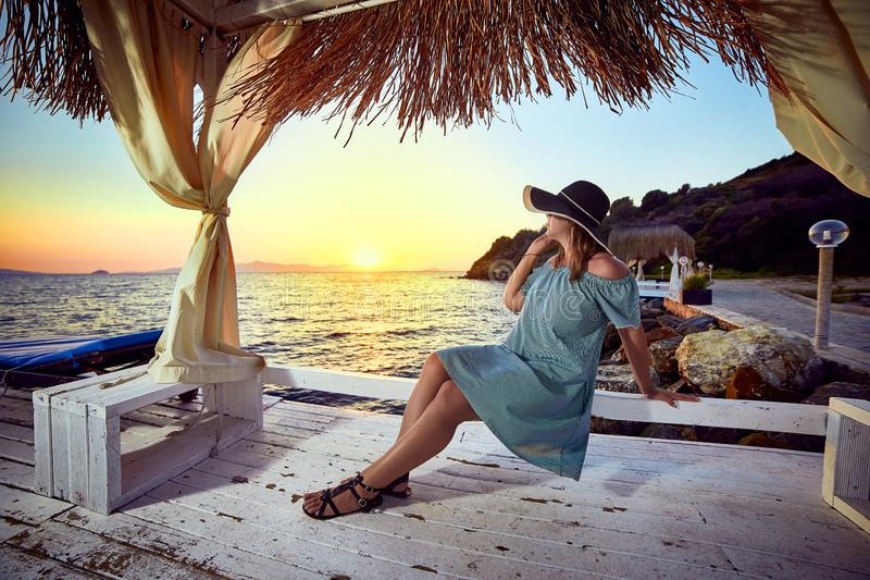 帽子的妇女放松由一种豪华海滩前的旅馆手段的海在日落享受完善的海滩假日假期的  免版税库存照片