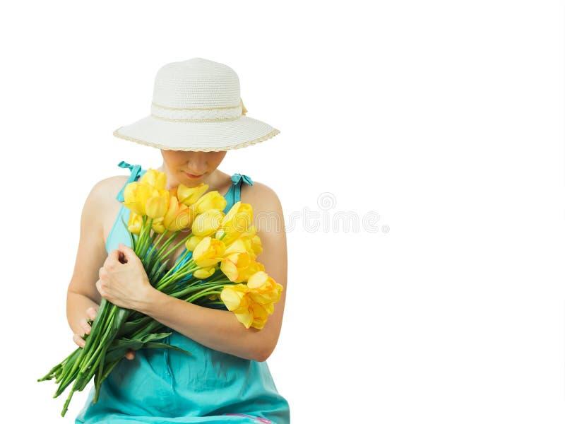 帽子的妇女有郁金香花束的与下来他的头的 图库摄影