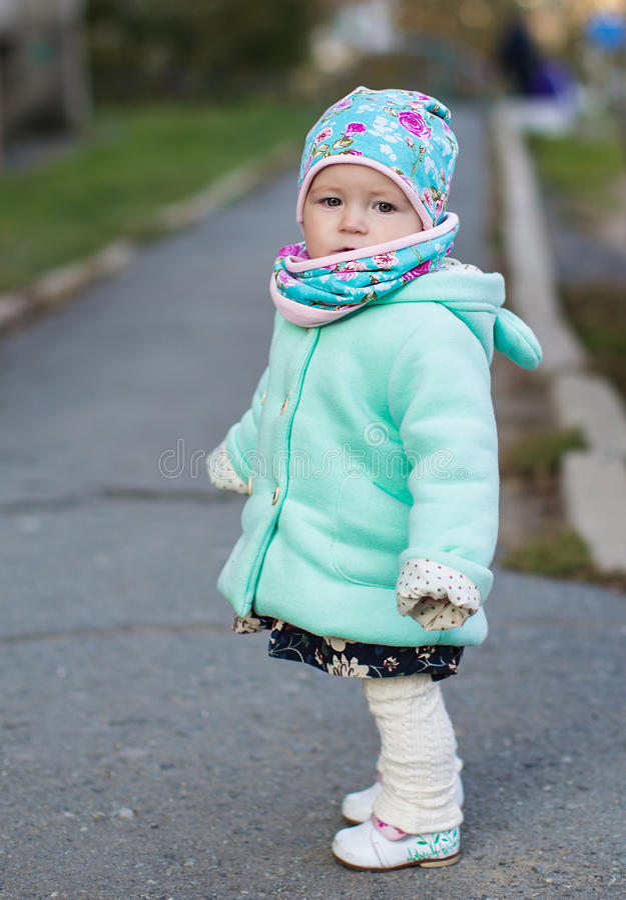 帽子的小女孩走在路的 库存照片