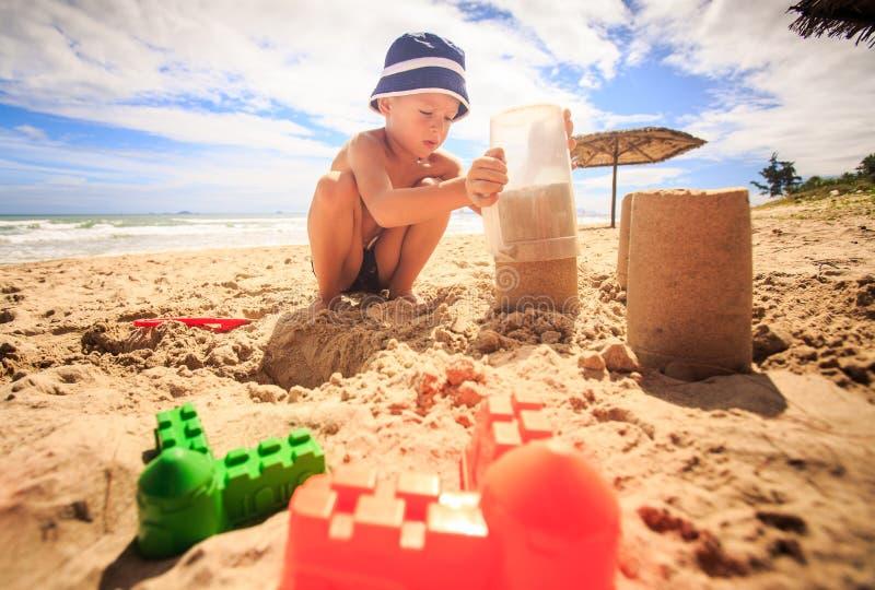 帽子的小男孩在玩具附近接触在塑料杯子的沙子在海滩 免版税库存照片