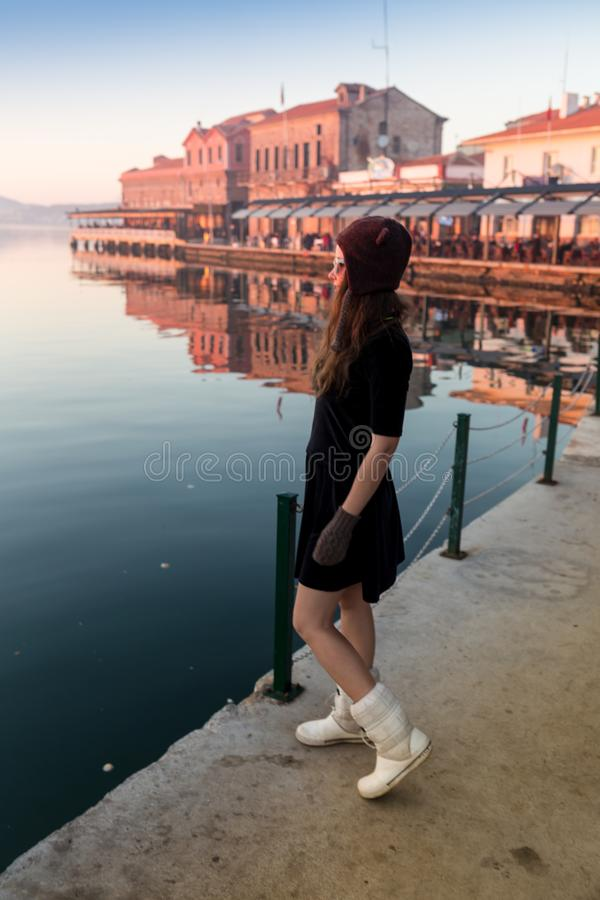 帽子的少妇和逗人喜爱的夏天穿戴在码头的身分有平安的镇风景的,看日落 免版税库存照片
