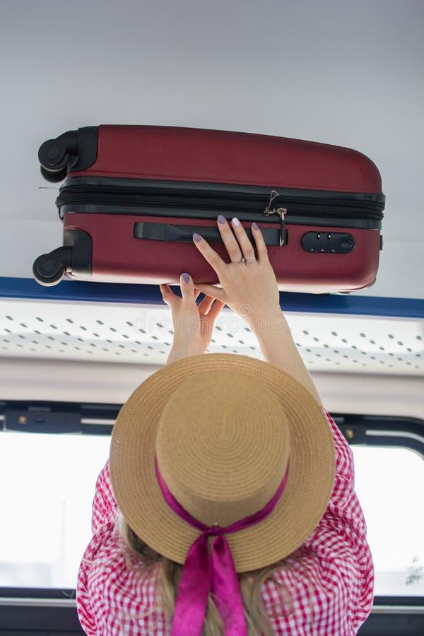 帽子的少妇旅客在架子顶部上把手提箱放在火车 库存照片