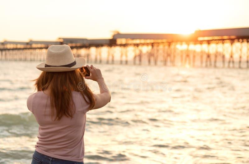 帽子的年轻亚裔妇女拍日落与聪明的海滩照片 免版税库存照片