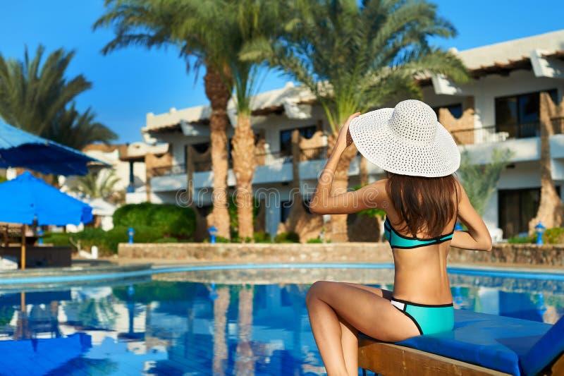 帽子的年轻女人坐太阳懒人在游泳场,概念时间附近旅行 在水池夏天放松 免版税图库摄影