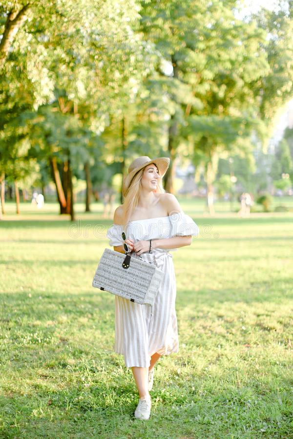 帽子的年轻犹特人妇女走在公园和保留袋子和太阳镜的 免版税库存图片