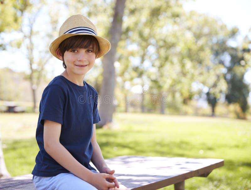 帽子的年轻男小学生坐公园长椅微笑对照相机的 免版税图库摄影