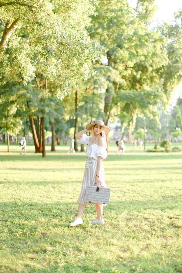 帽子的年轻美国妇女走在公园和保留袋子和太阳镜的 库存照片