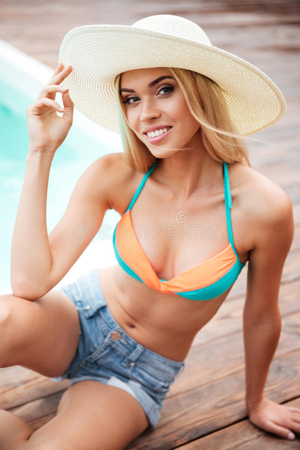 帽子的微笑的少妇和短裤临近游泳池 免版税库存图片