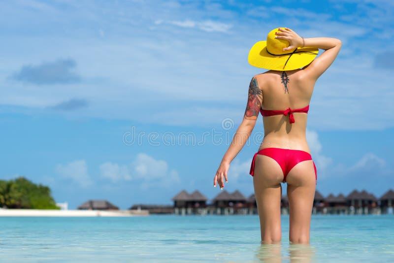 帽子的性感的妇女在热带海滩 免版税图库摄影