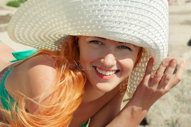 帽子的愉快的女孩在海滩 免版税库存图片