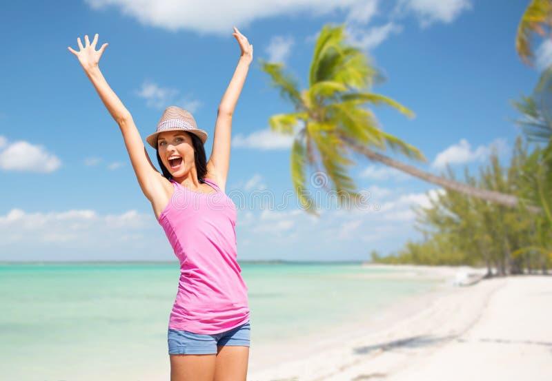 帽子的愉快的少妇在夏天海滩 免版税库存图片
