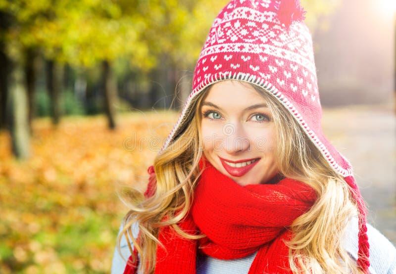 帽子的愉快的微笑的妇女在秋天背景 免版税库存图片