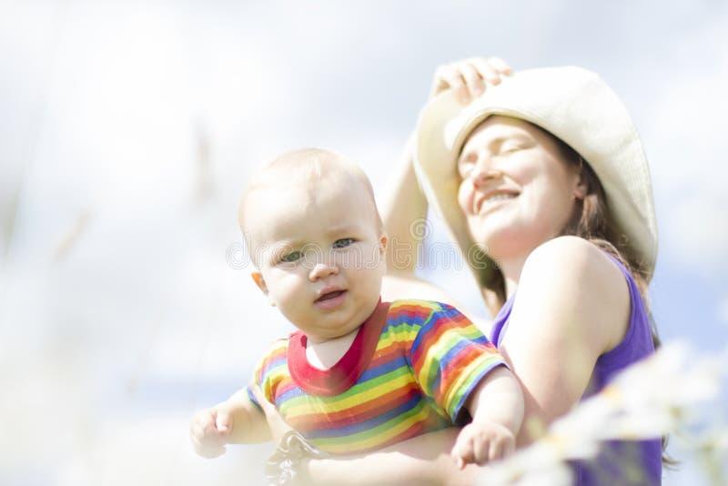 帽子的愉快的母亲有他的小儿子的在室外的夏天 库存图片