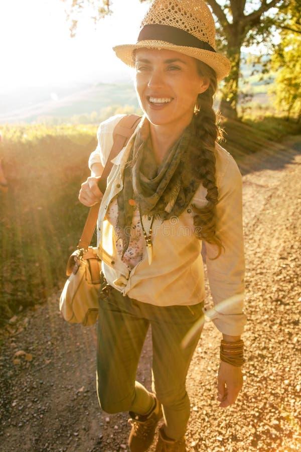 帽子的愉快的活跃妇女远足者在托斯卡纳远足 库存图片