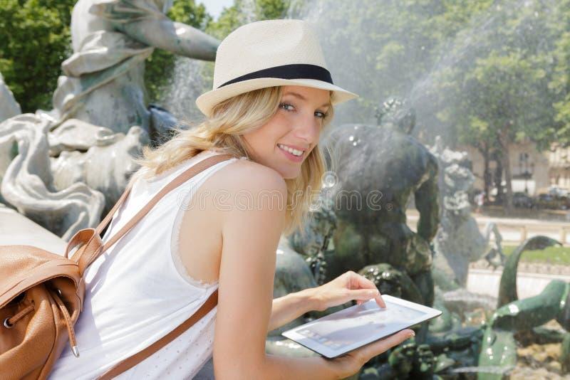 帽子的愉快的白肤金发的年轻女人使用片剂在户外 库存照片