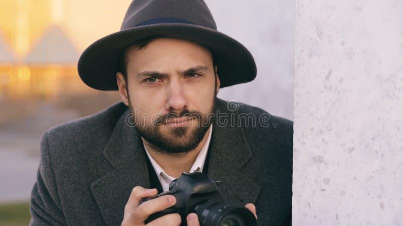 帽子的拍摄在照相机的年轻无固定职业的摄影师人特写镜头名人,当在墙壁后时的间谍 库存图片
