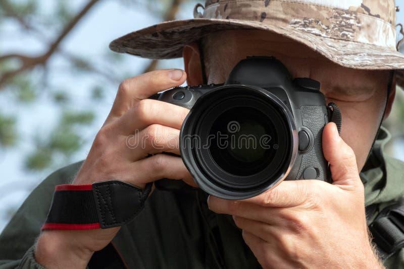 帽子的旅客摄影师调查镜头 生活方式,照片故事,自然摄影 r 免版税库存照片
