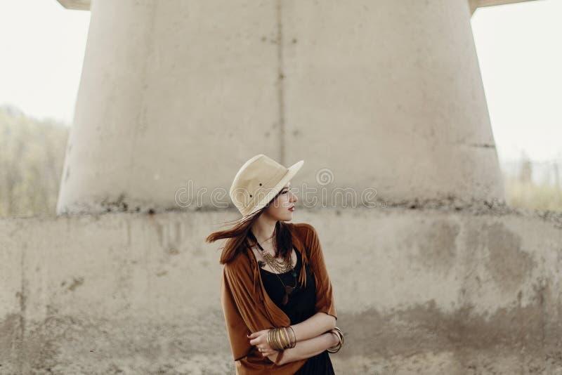 帽子的时髦的行家妇女有摆在河s附近的有风头发的 免版税库存图片