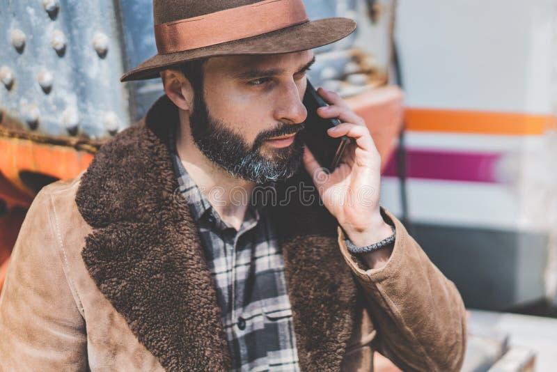 帽子的有胡子的人谈话在一个手机 使用智能手机的偶然专业企业家外面 免版税图库摄影