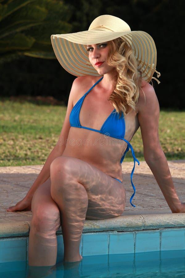 帽子的比基尼泳装妇女由水池 免版税库存照片