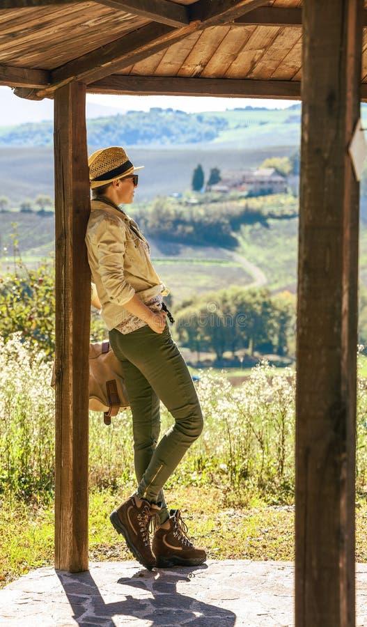 帽子的活跃妇女远足者在托斯卡纳享受风景的 库存图片
