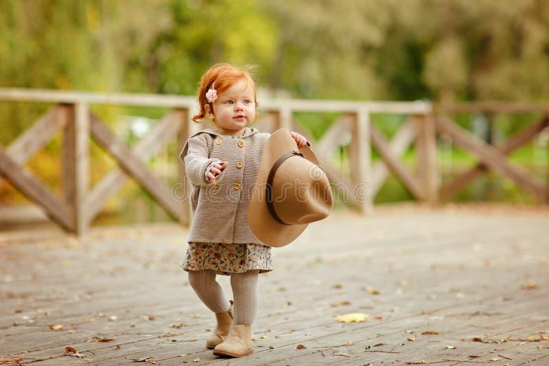 帽子的红发女婴微笑户外在秋天的 库存照片