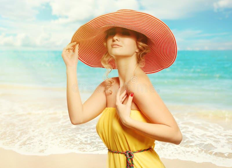 帽子的美丽的女孩享用在海滩的太阳。 免版税库存图片