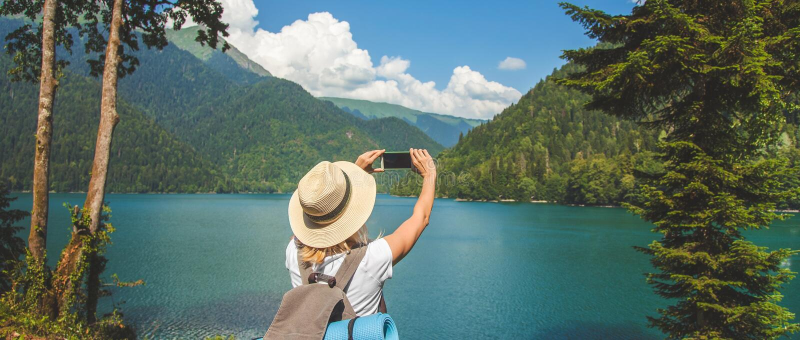 帽子的美丽的女孩旅客在湖站立并且拍在山旅行概念暑假C背景的照片  库存照片