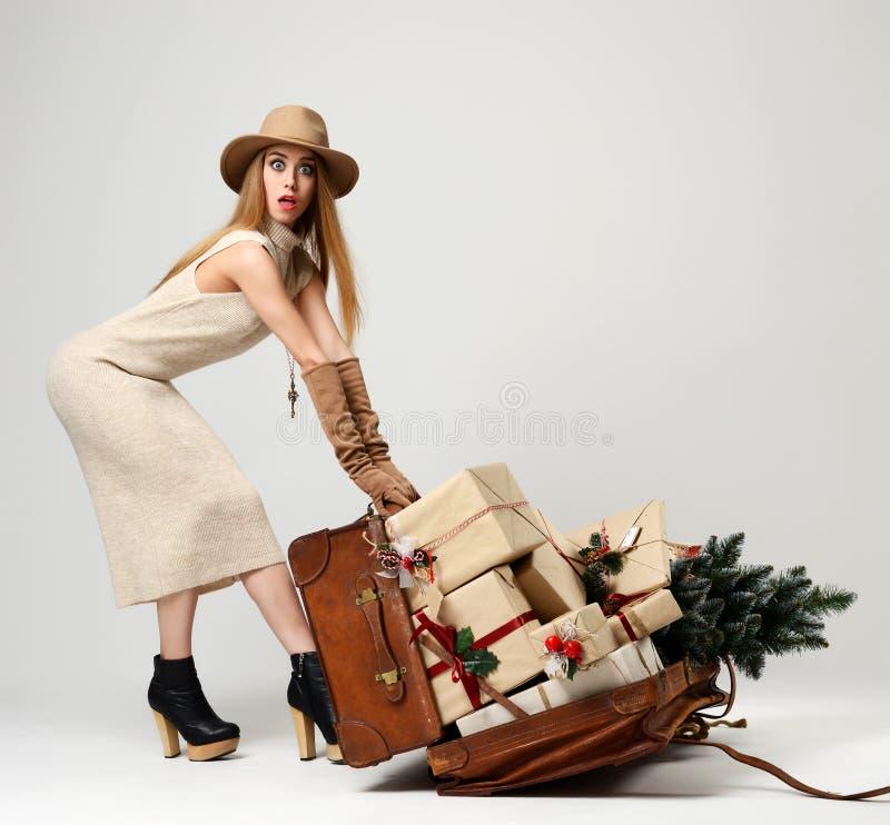 帽子的美丽的妇女旅客有大开放皮革减速火箭的袋子的有很多圣诞节礼物礼物惊奇 免版税图库摄影