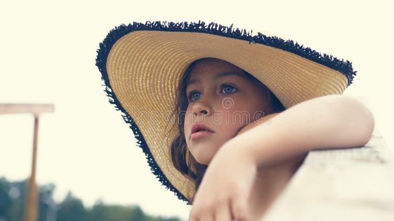 帽子的美丽的小女孩坐导致海和神色的台阶入距离 免版税库存照片