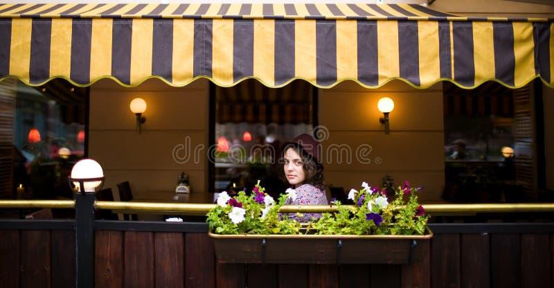 帽子的美丽的少妇坐在咖啡馆的一个大阳台并且看照相机 免版税库存图片