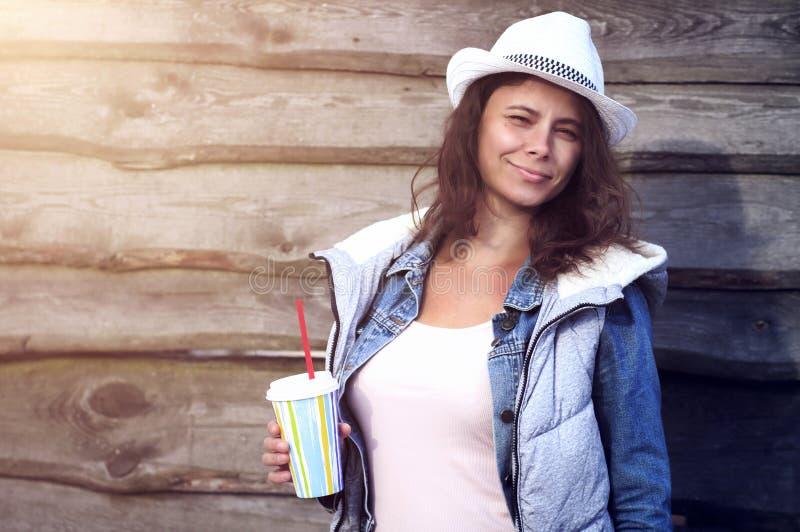 帽子的美丽的被晒黑的女孩对拿着与秸杆的木墙壁鸡尾酒在玻璃 可爱的妇女夏天心情  免版税库存图片