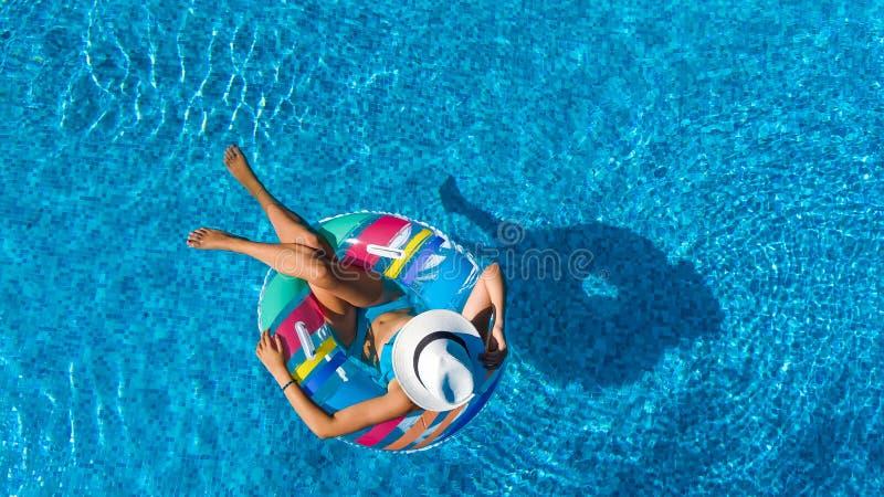 帽子的美女在从上面游泳场空中顶视图,妇女在可膨胀的圆环多福饼放松并且游泳并且获得乐趣 免版税库存照片