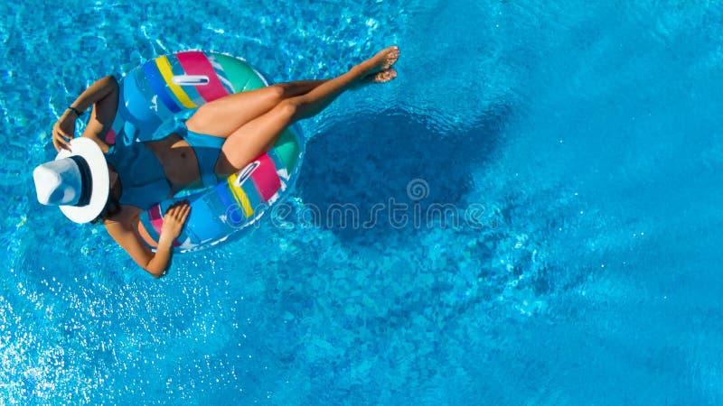 帽子的美女在从上面游泳场空中顶视图,妇女在可膨胀的圆环多福饼放松并且游泳并且获得乐趣 图库摄影