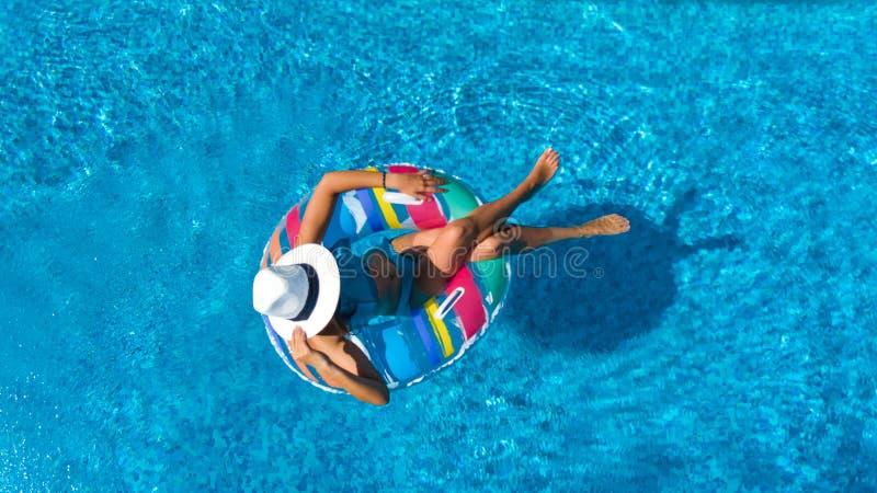 帽子的美女在从上面游泳场空中顶视图,妇女在可膨胀的圆环多福饼放松并且游泳并且获得乐趣 库存照片