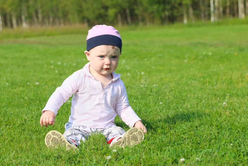 帽子的逗人喜爱的愉快的女婴坐绿草 库存照片