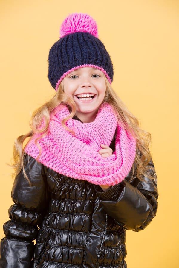 帽子的,桃红色围巾,在橙色背景的黑夹克女孩 免版税库存照片