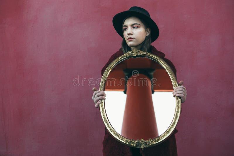 帽子藏品镜子的青少年女孩在红色墙壁前面 镜子反射修造的对面的专栏 免版税库存照片