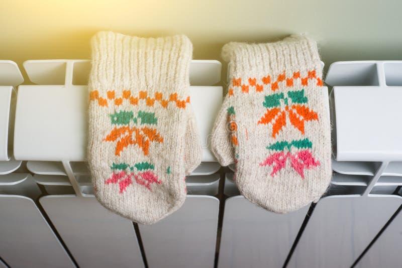 幅射器与被编织的婴孩手套的热化盘区 免版税库存照片