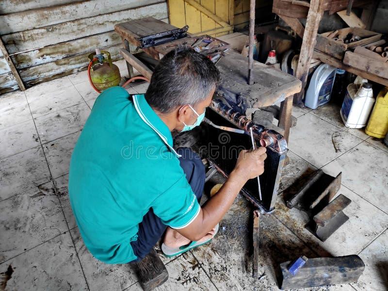 幅射器安装工,当清洗和修理在老汽车时的残破的幅射器 免版税库存图片