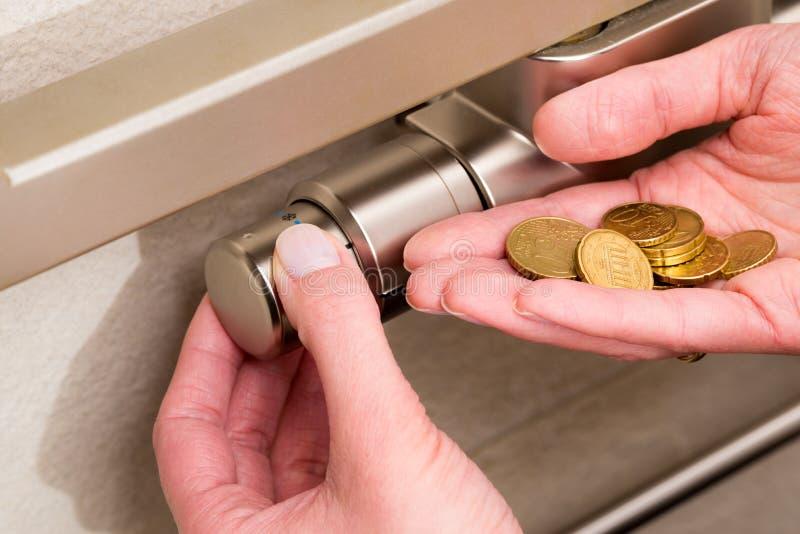 幅射器温箱、硬币和手 免版税库存图片