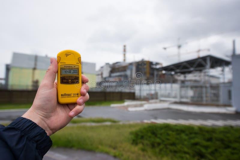 幅射计在手中有在背景的第四台反应器的 免版税图库摄影