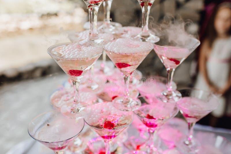 干冰马蒂尼鸡尾酒玻璃金字塔用红色樱桃 免版税库存图片