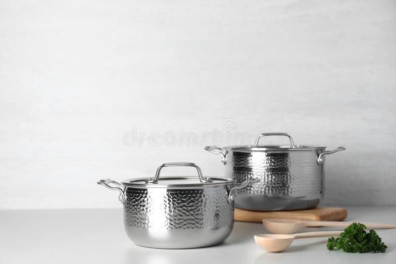 干净的平底深锅和匙子在桌上反对轻的背景 免版税库存图片