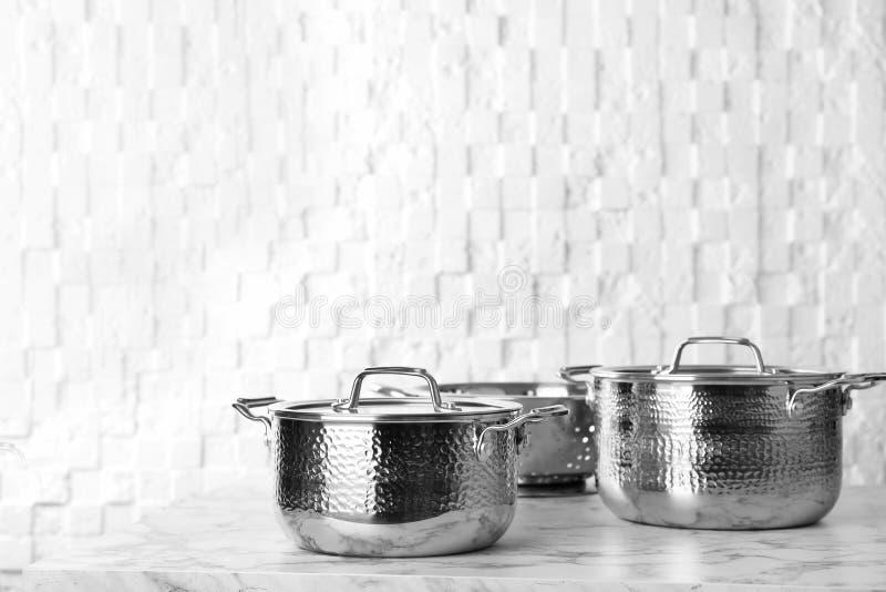 干净的平底深锅和滤锅在桌上对白色墙壁 免版税图库摄影